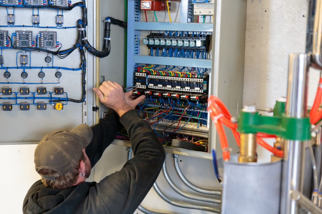 Electrician working on the service panel at a craft brewery commercial building.