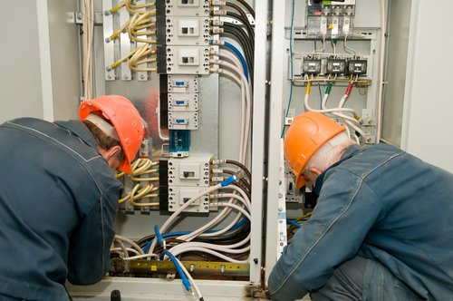 Electricians fixing industrial circuit lines