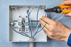 Electrician using wire stripper to prepare the panel outlet