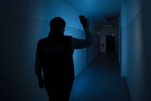 Security guard holding a flashlight in the hallway with no electricity on.